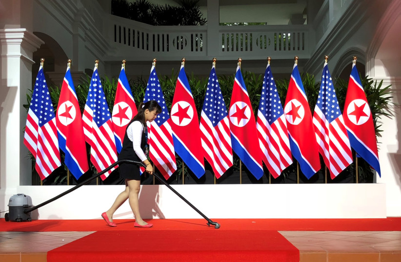A worker vacuums the stage at the spot where U.S. President Donald Trump and North Korea's leader Kim Jong Un are expected to meet and shake hands for the first time at the start of their summit at the Capella Hotel on Singapore's resort island of Sentosa in Singapore June 12, 2018. (photo credit: JONATHAN ERNST / REUTERS)