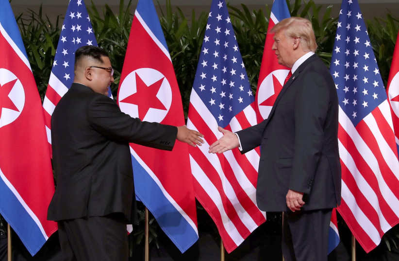 U.S. President Donald Trump shakes hands with North Korean leader Kim Jong Un at the Capella Hotel on Sentosa island in Singapore June 12, 2018.  (photo credit: JONATHAN ERNST / REUTERS)