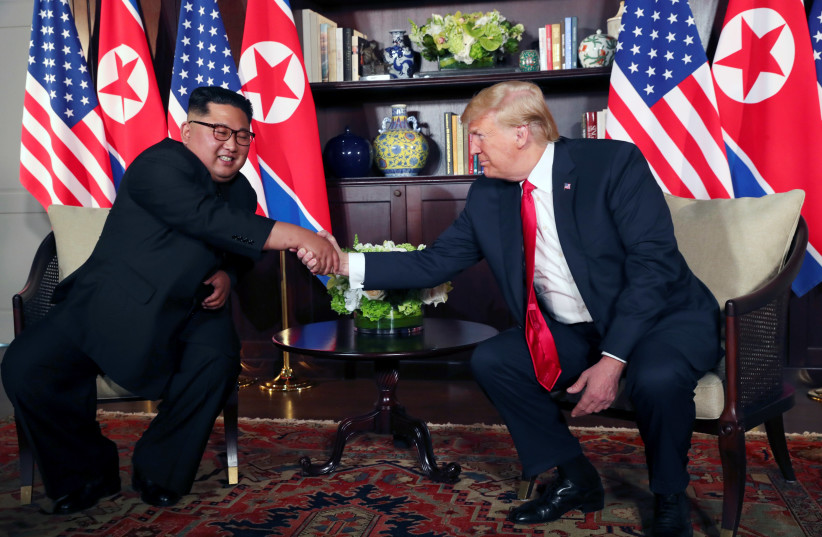 U.S. President Donald Trump shakes hands with North Korea's leader Kim Jong Un before their bilateral meeting at the Capella Hotel on Sentosa island in Singapore June 12, 2018. (photo credit: JONATHAN ERNST / REUTERS)