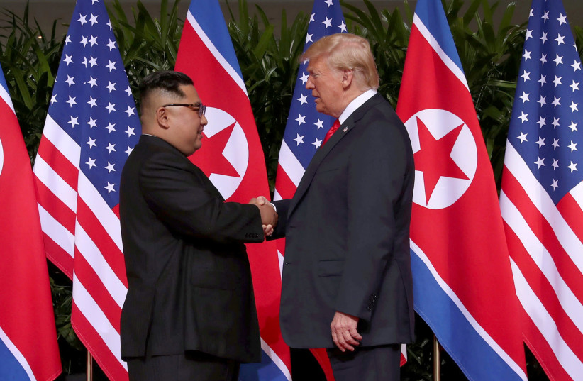U.S. President Donald Trump and North Korea's leader Kim Jong Un walk during their summit at the Capella Hotel on Sentosa island in Singapore (photo credit: ANTHONY WALLACE/POOL VIA REUTERS)