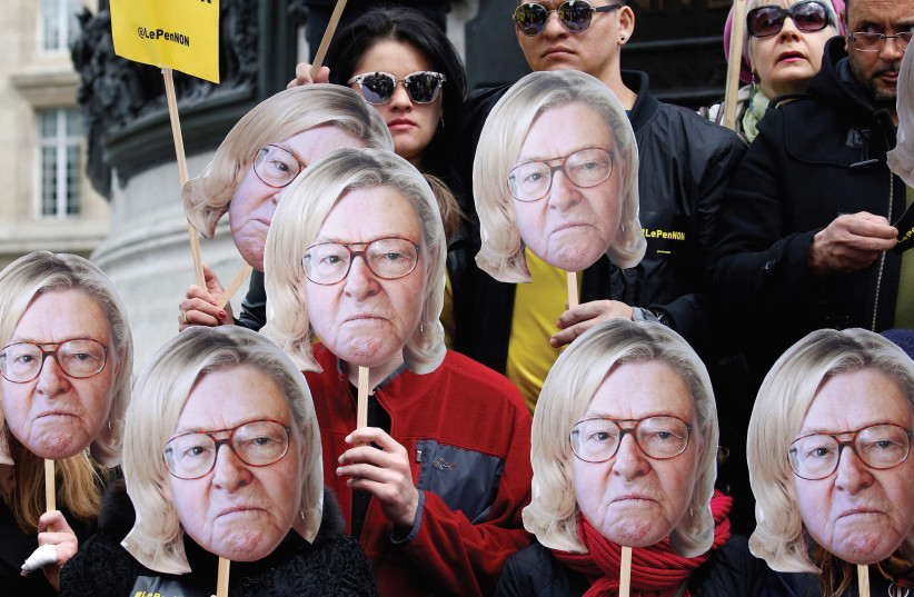 ACTIVISTS WEAR masks depicting the face of Jean-Marie Le Pen, the founder of the French far-right National Front, with the hair of current party leader, his daughter Marine Le Pen, during a demonstration last year. (photo credit: GONZALO FUENTES / REUTERS)