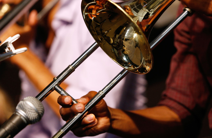 A musician plays a trombone during the first day of the New Orleans Jazz and Heritage Festival in New Orleans, Louisiana April 25, 2014. (photo credit: JONATHAN BACHMAN/REUTERS)