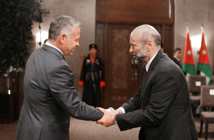 Jordan's King Abdullah II shakes hands with Prime Minister Omar al-Razzaz during a swearing-in ceremony of the new cabinet in Amman, Jordan June 14, 2018. (photo credit: REUTERS)