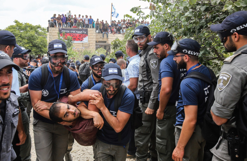Security forces evict a demonstrator from Netiv Ha'avot on Tuesday (photo credit: MARC ISRAEL SELLEM/THE JERUSALEM POST)