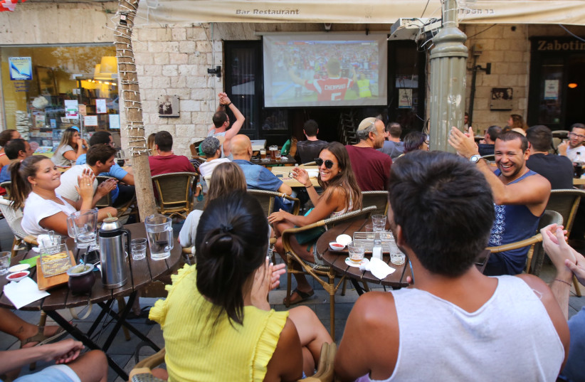 Fans sitting in a bar in Jerusalem watching the first game of the 2018 World Cup (photo credit: MARC ISRAEL SELLEM)