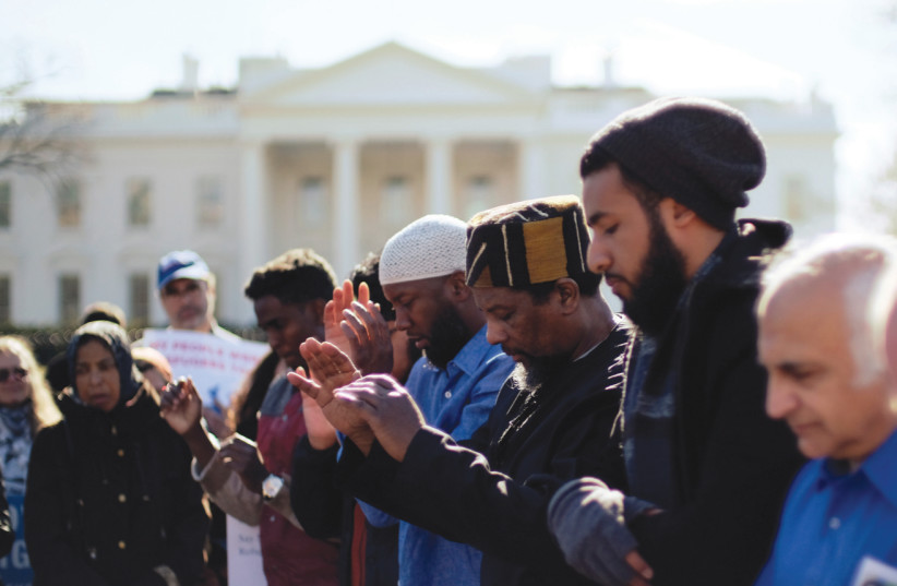 GROUPS INCLUDING the Council on American-Islamic Relations, MoveOn.org, Oxfam, and the ACLU hold a rally and prayer service in front of the White House to mark the anniversary of the first Trump administration travel and refugee ban in January (photo credit: REUTERS/JAMES LAWLER DUGGAN)