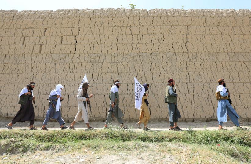Taliban walk as they celebrate ceasefire in Ghanikhel district of Nangarhar province, Afghanistan  (photo credit: PARWIZ PARWIZ/REUTERS)