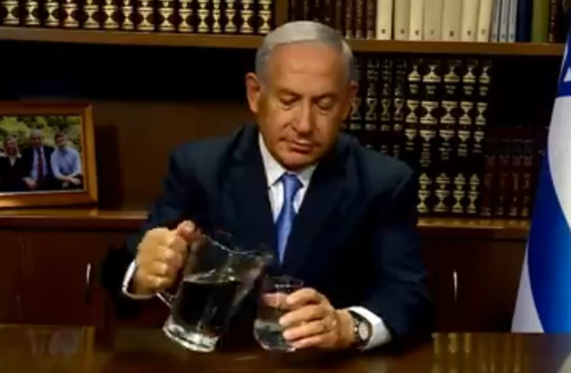 Prime Minister Benjamin Netanyahu pouring water during a video aimed at the people of Iran.   (photo credit: screenshot)