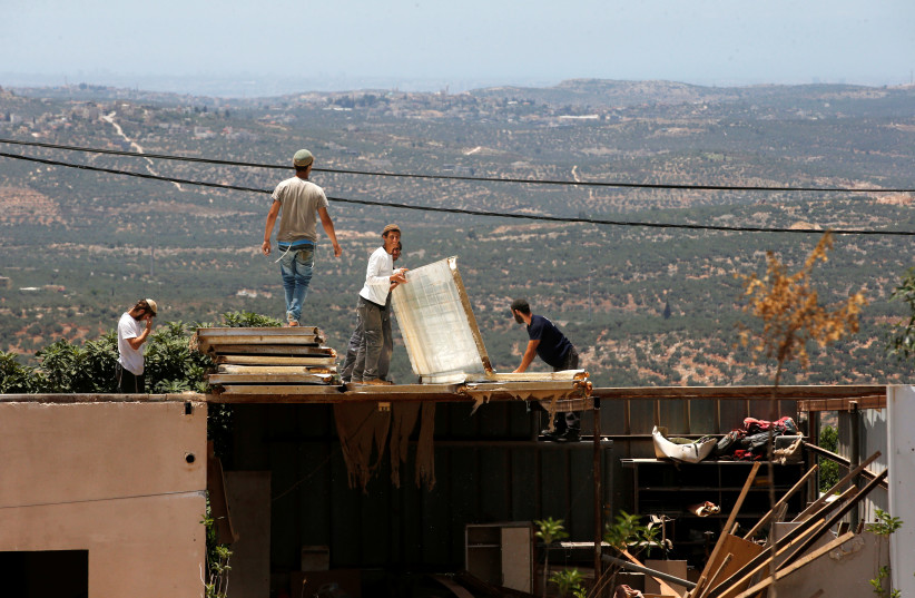 Jewish settlers dismantle parts of a structure during the eviction of buildings that an Israeli court deemed to have been built illegally in the Tapuach West outpost, in the West Bank, June 17, 2018. (photo credit: RONEN ZVULUN/ REURERS)