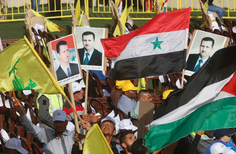 Supporters of Lebanon's Hezbollah leader Sayyed Hassan Nasrallah carry flags and pictures of Syria's President Bashar al-Assad during a rally marking al-Quds Day, (Jerusalem Day) in Maroun Al-Ras village, near the border with Israel, southern Lebanon (photo credit: AZIZ TAHER/REUTERS)