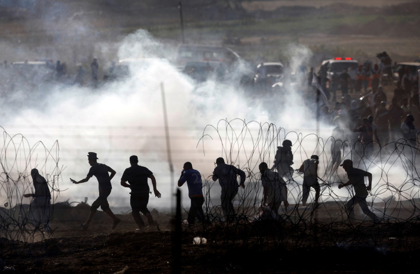 Palestinians protesting on the Gaza side of the border between Israel and Gaza, June 2018 (photo credit: AMIR COHEN/REUTERS)