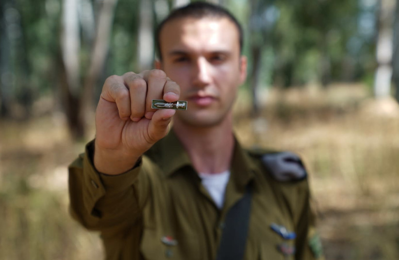 Soldier holding the newly designed pin (photo credit: COURTESY IDF SPOKESMAN'S OFFICE)