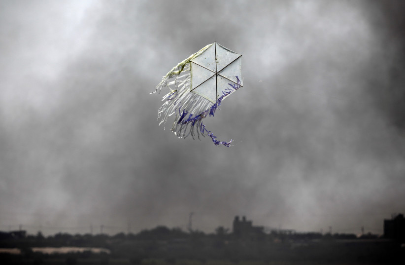 A kite flies over the border in an area where kites and balloons have caused blazes, between Israel and the Gaza strip June 8, 2018.  (photo credit: AMIR COHEN - REUTERS)