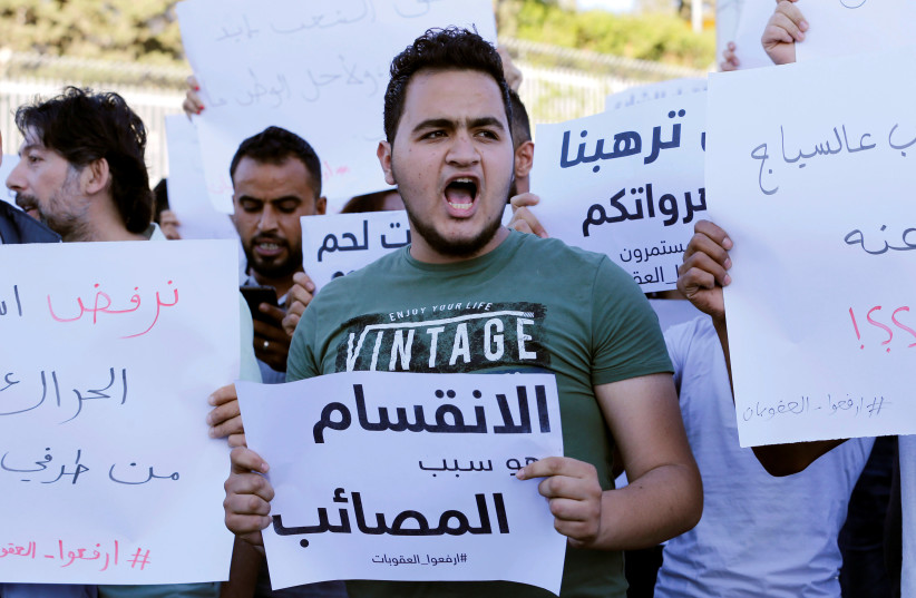 """A Palestinian demonstrator holds a sign that reads """"division is the reason for adversities"""" during a protest demanding President Mahmoud Abbas to lift the sanctions on Gaza Strip, in Bethlehem, June 20, 2018 (photo credit: MUSSA QAWASMA / REUTERS)"""