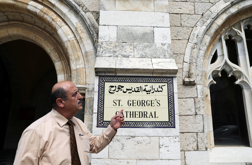 A church official gestures as he stands next to the entrance to the Anglican St. George's Cathedral in Jerusalem, June 13, 2018 (photo credit: REUTERS/AMMAR AWAD)