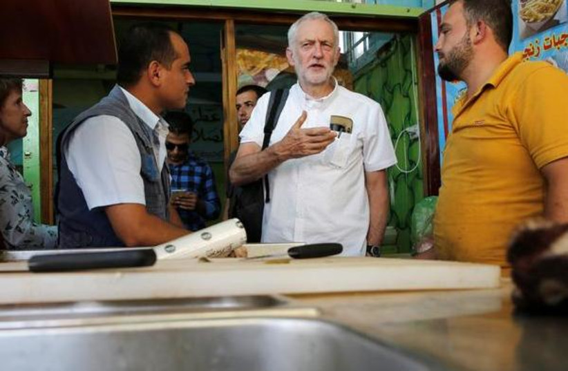 Britain's opposition leader Jeremy Corbyn during his visit to Al Zaatari refugee camp, in the Jordanian city of Mafraq, near the border with Syria, June 22, 2018 (photo credit: MUHAMMAD HAMED / REUTERS)