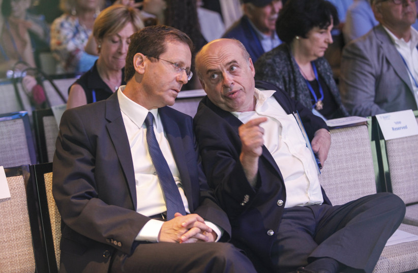 Outgoing Jewish Agency Chairman Natan Sharansky and Chairman-elect MK Isaac Herzog share a moment following Herzog's election at the Jewish Agency Board of Governors' meetings in Jerusalem, June 24, 2018.  (photo credit: JEWISH AGENCY)