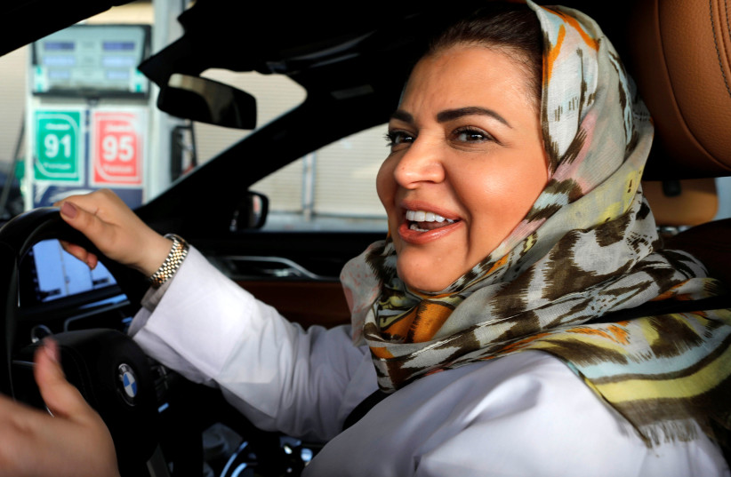 Samira al-Ghamdi, a practicing psychologist, smiles while making a stop to refuel her car as she drives to work in Jeddah, Saudi Arabia June 24, 2018. (photo credit: ZOHRA BENSEMRA/REUTERS)