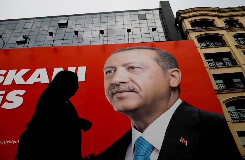 A woman passes by an election poster of Turkey's President Tayyip Erdogan in Istanbul, Turkey (photo credit: ALKIS KONSTANTINIDIS / REUTERS)