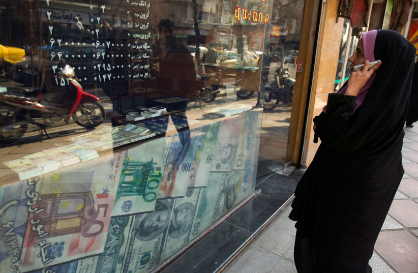 A woman looks at exchange rates by the window of a currency exchange shop in Tehran's business district, Iran (photo credit: RAHEB HOMAVANDI/REUTERS)