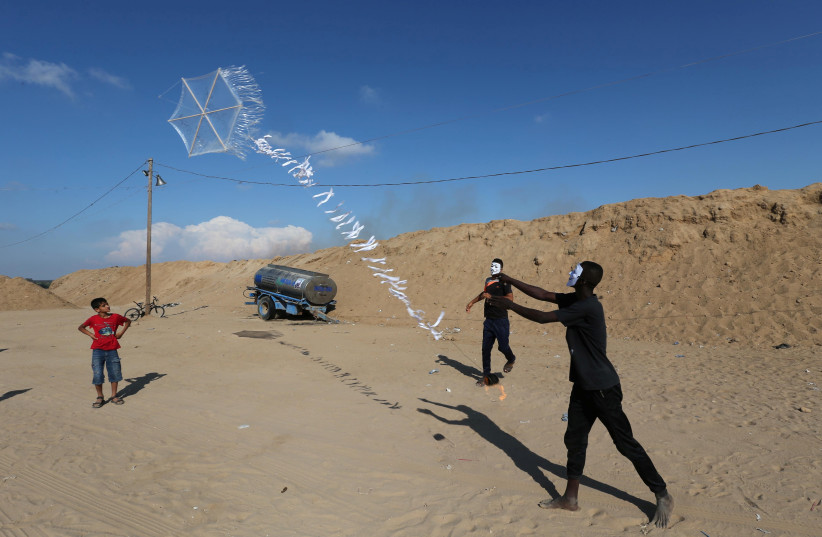 Palestinians in central Gaza fly a kite loaded with flammable material to be thrown at Israel (photo credit: IBRAHEEM ABU MUSTAFA/REUTERS)
