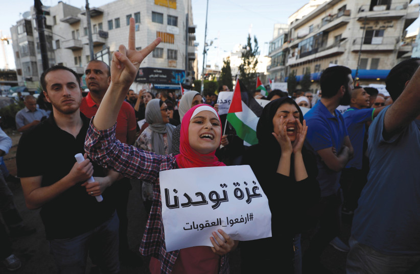 A Palestinian protester holds up a sign that reads 'Gaza unites us,' during a demonstration in Ramallah calling on Palestinian Authority President Mahmoud Abbas to lift sanctions on the Gaza Strip (photo credit: REUTERS)
