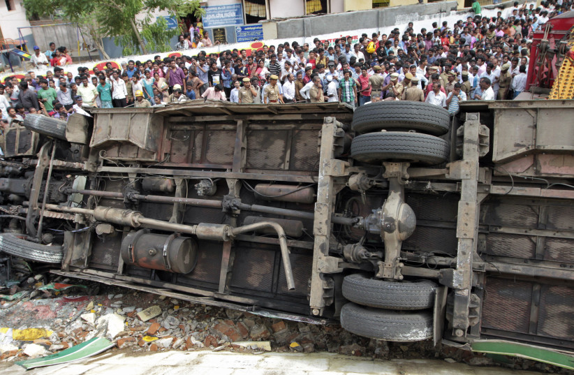 Onlookers stand next to an overturned passenger bus at the site of an accident in the southern Indian city of Chennai June 27, 2012. More than 30 passengers of a Metropolitan Transport Corporation bus were injured after the bus overturned and fell off a flyover, local media reported on Wednesday.  (photo credit: REUTERS)