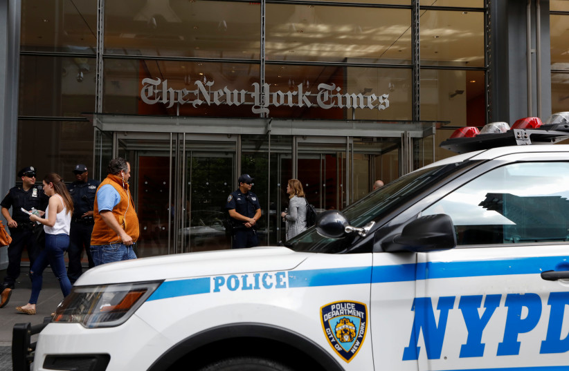New York Police officers are seen deployed outside the New York Times building following a fatal shooting at a Maryland newspaper, in New York City, U.S., June 28, 2018.  (photo credit: BRENDAN MCDERMID/REUTERS)