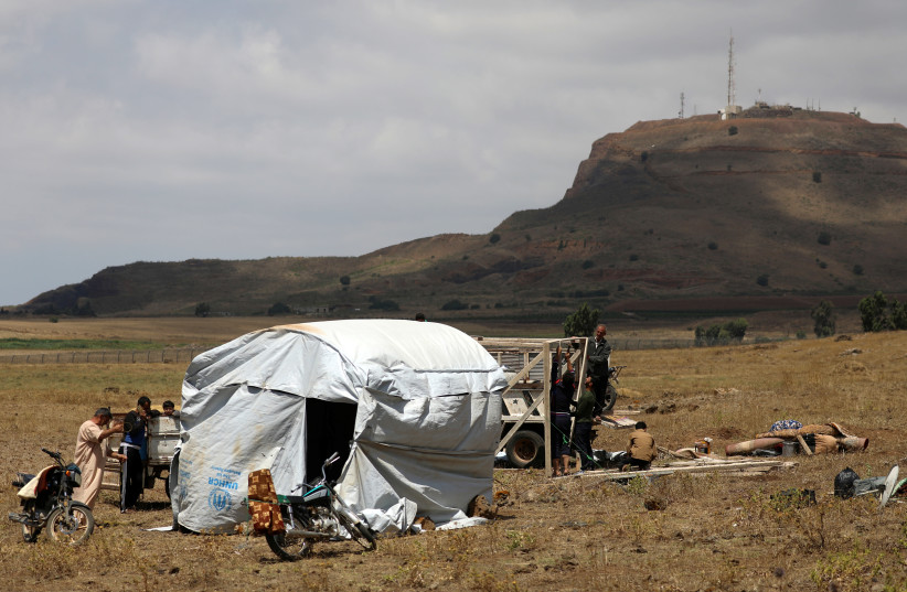 Internally displaced people from Deraa province erect a tent near the Golan Heights in Quneitra, Syria June 29, 2018 (photo credit: REUTERS/ALAA AL-FAQIR)