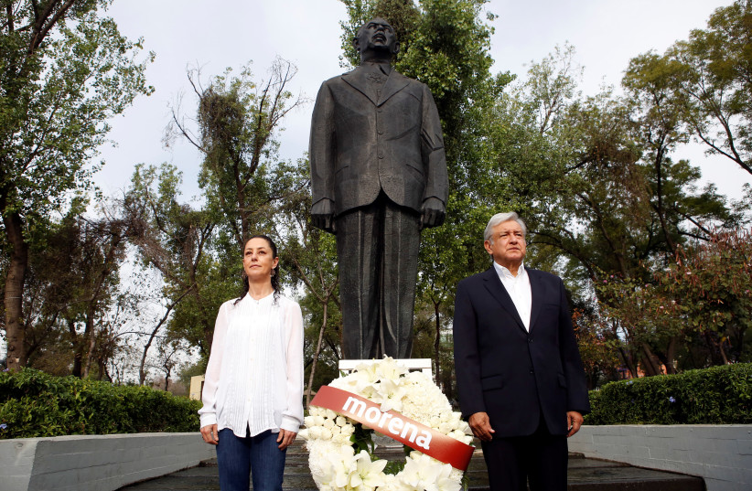 Andres Manuel Lopez Obrador, presidential candidate of the National Regeneration Movement (MORENA), offers a floral tribute to commemorate the 80th anniversary of the expropriation of Mexico's oil industry, next to Claudia Sheinbaum Pardo, candidate for Mexico City Mayor by the National Regeneration (photo credit: GINNETTE RIQUELME/ REUTERS)