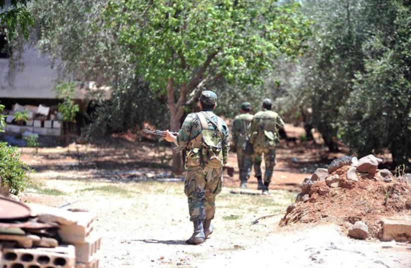 Forces loyal to Syria's President Bashar al-Assad walk in al-Ghariya al-Gharbiya in Deraa province, Syria in this handout released on June 30, 2018 (photo credit: SANA/HANDOUT VIA REUTERS)