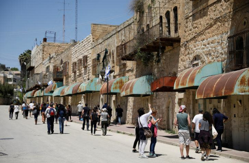 """Visitors on a tour held by leftwing NGO """"Breaking the Silence"""" walk down Shuhada street in the West Bank city of Hebron April 19, 2017 (photo credit: REUTERS/AMIR COHEN)"""