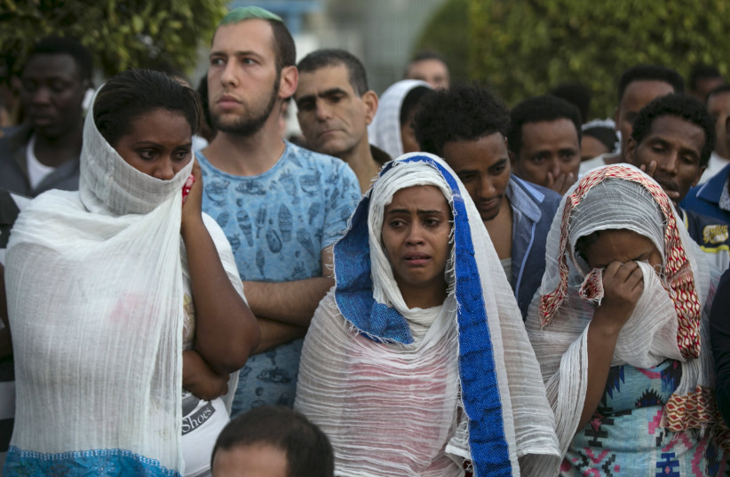 Israelis and fellow community members attend a memorial ceremony for Habtom Zarhum, an Eritrean migrant who was mistaken for a gunman at a shooting attack, in Tel Aviv, Israel October 21, 2015. (photo credit: REUTERS/BAZ RATNER)
