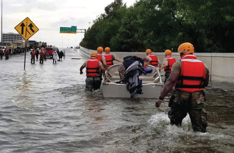 TEXAS ARMY National Guard soldiers move through flooded Houston streets as floodwaters from Hurricane Harvey rise, on August 28, 2017 (photo credit: Wikimedia Commons)