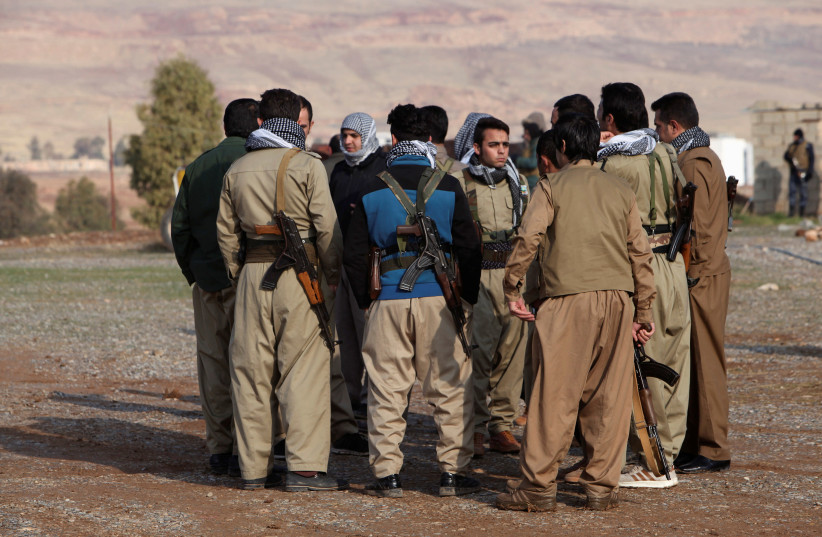 Members of the Democratic Party of Iranian Kurdistan (PDKI) gather during a funeral of victims who were killed in a bomb attack at the offices of the PDKI in Koy Sanjak, east of Erbil, Iraq, December 21, 2016 (photo credit: REUTERS/AZAD LASHKARIG)