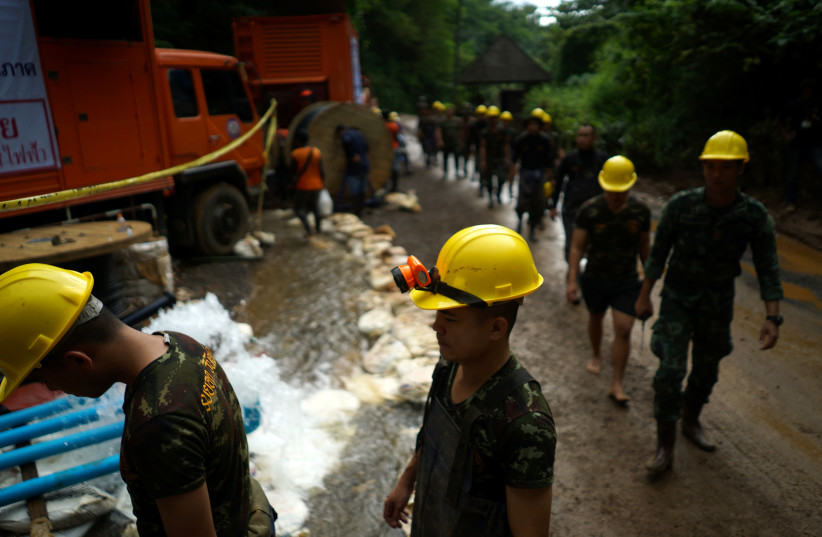 Military personnel walk in line as they prepare to enter the Tham Luang cave complex, where 12 boys and their soccer coach are trapped, in the northern province of Chiang Rai, Thailand, July 6, 2018 (photo credit: REUTERS/ATHIT PERAWONGMETHA)