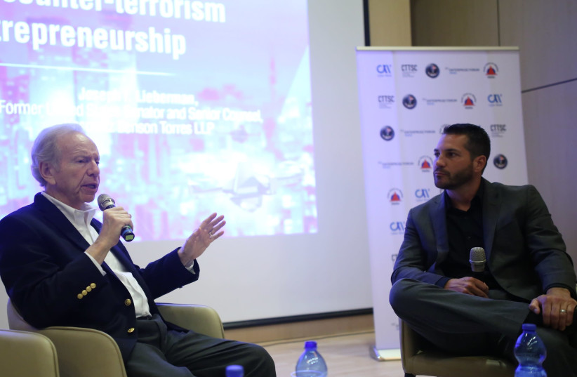 Adam Tarsi (R) in conversation with former Senator Joe Lieberman (L) at the Combating Terrorism Technology Conference (photo credit: DROR SITHAKOL)