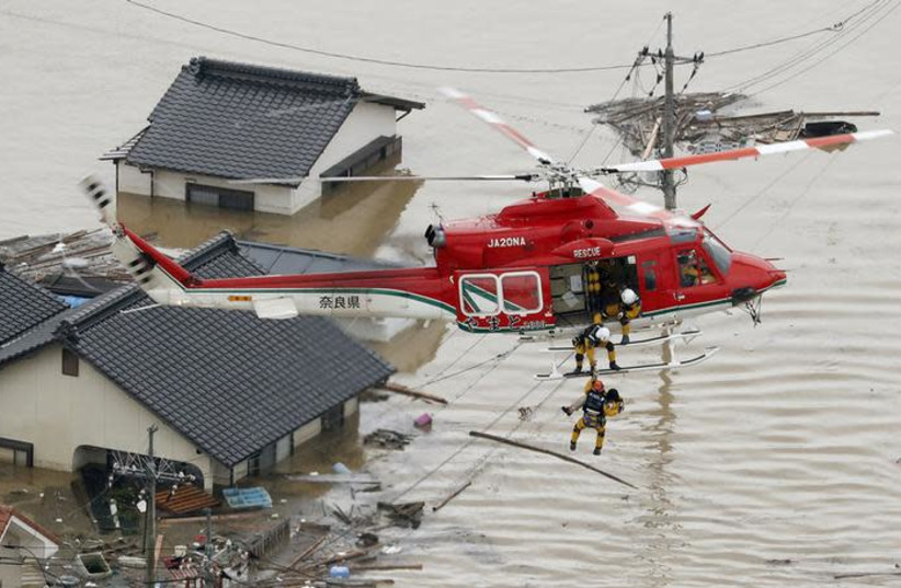 An aerial view shows a local resident being rescued from a submerged house by rescue workers using helicopter at a flooded area in Kurashiki, southern Japan, in this photo taken by Kyodo July 7, 2018 (photo credit: KYODO/VIA REUTERS)