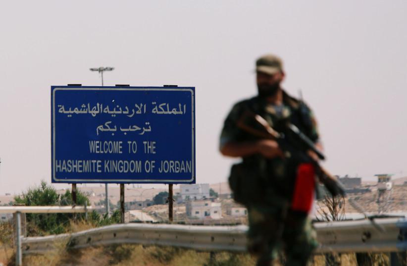 A Syrian soldier is seen standing in the Nasib border crossing with Jordan in Deraa, Syria July 7, 2018.  (photo credit: OMAR SANADIKI/REUTERS)