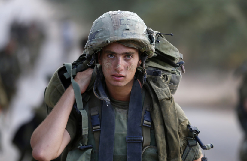 An Israeli soldier from the Nahal Brigade carries equipment after returning to Israel from Gaza August 5, 2014 (photo credit: REUTERS/BAZ RATNER)