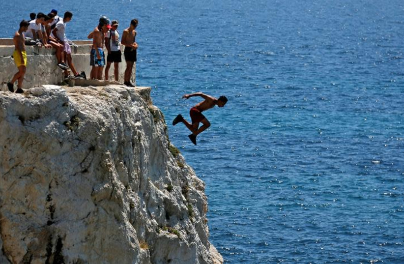 A teenager dives into the Mediterranean Sea (photo credit: REUTERS/JEAN-PAUL PELISSIER)
