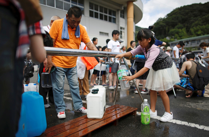 Local residents receive emergency water supply near a flooded area at Mihara Daini junior high school, Japan, July 9, 2018. (photo credit: REUTERS/ISSEI KATO)