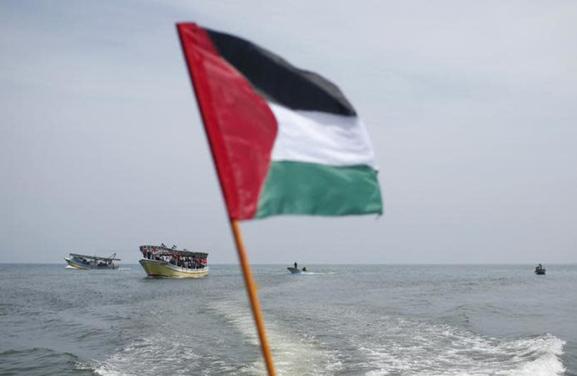 A Palestinian flag flutters as activists ride a boat during a rally ahead of the 4th anniversary of the Mavi Marmara Gaza flotilla incident, at the seaport of Gaza City May 29, 2014 (photo credit: REUTERS/MOHAMMED SALEM)