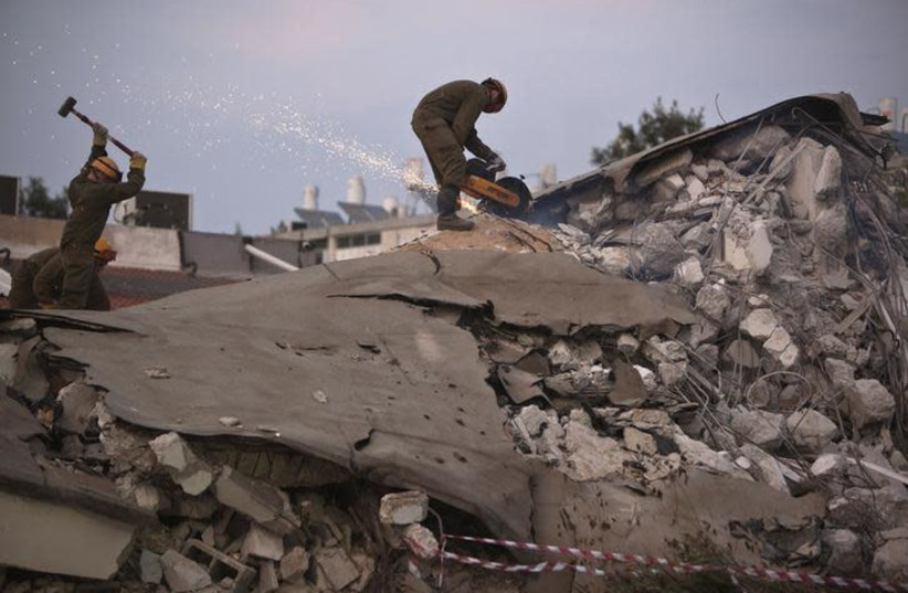 Israeli soldiers from the Home Front Command stand on rubble as they take part in an earthquake drill in Holon, near Tel Aviv October 21, 2012 (photo credit: REUTERS/NIR ELIAS)