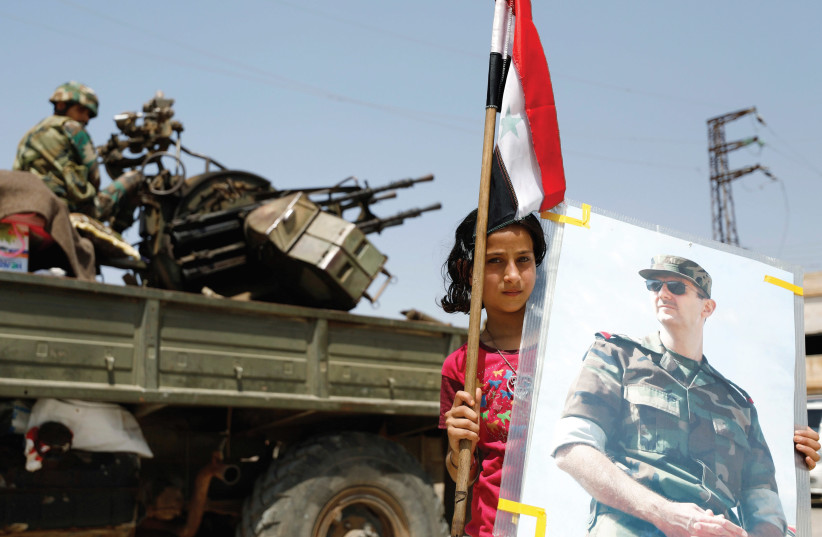 A GIRL holds an image of Syrian President Bashar Assad. (photo credit: REUTERS)