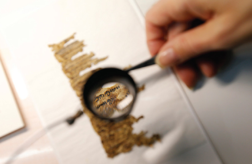 A restorer works on a fragment of the Dead Sea Scrolls in a laboratory at the Israel Museum in Jerusalem (photo credit: RONEN ZVULUN/REUTERS)
