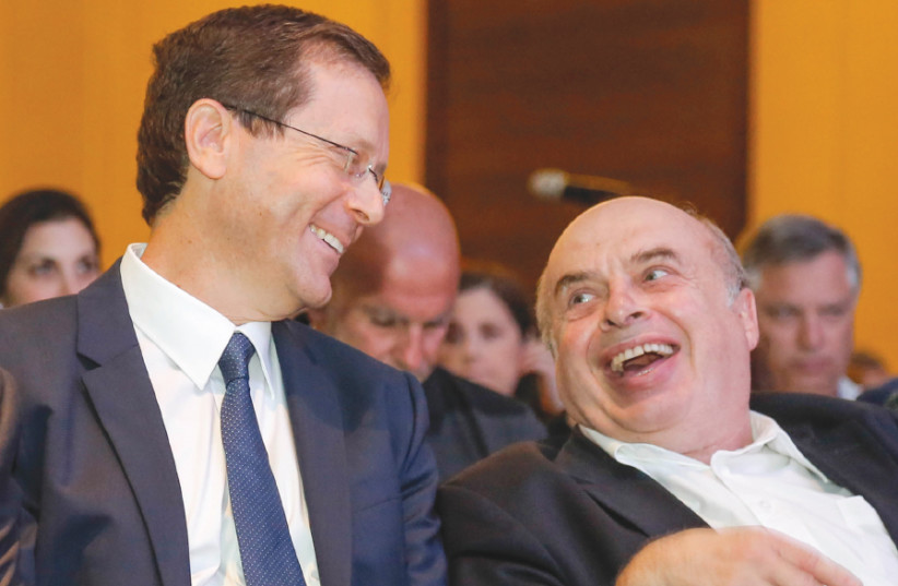 Isaac Herzog shares a laugh with Natan Sharansky following Herzog's election as chairman of the Jewish Agency at the Board of Governors meeting in Jerusalem on June 24, 2018 (photo credit: NIR KAFRI/JAF)
