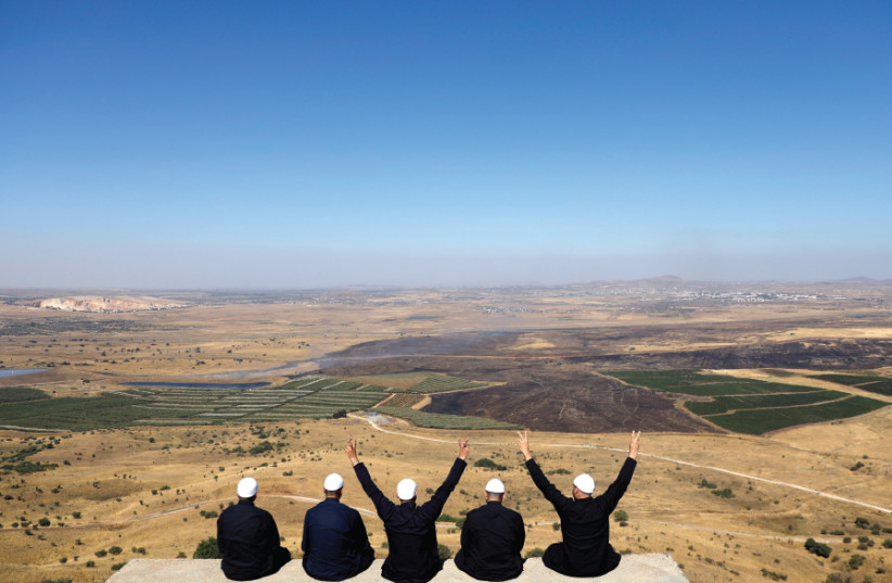 Israeli Druze watch the Syrian side of the Israel- Syria border on the Golan Heights on July 7, 2018 (photo credit: RONEN ZVULUN/REUTERS)