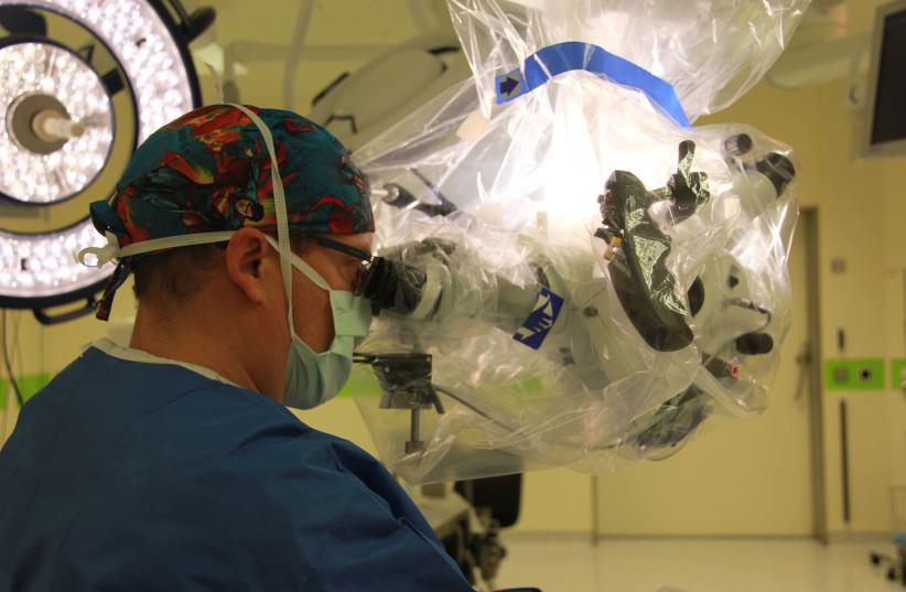 A neurosurgeon looks through an eyepiece on the KINEVO 900 microscope at Hadassah Ein Kerem (photo credit: HADASSAH SPOKESPERSON)