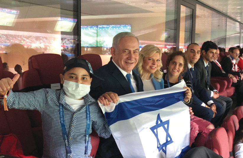 Prime Minister Benjamin Netanyahu and his wife, Sara, proudly display Israel's flag at the World Cup semifinal game between England and Croatia in Moscow on Wednesday, flanked by cancer patients Alon Eizarayev, 13 (left), and Mika Lipsker, 18, who went with them to Russia July 12, 2018 (photo credit: Courtesy)
